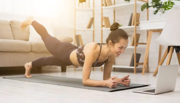 Mädchen-Training zu Hause, tun Planke und Videos auf Laptop ansehen – Foto