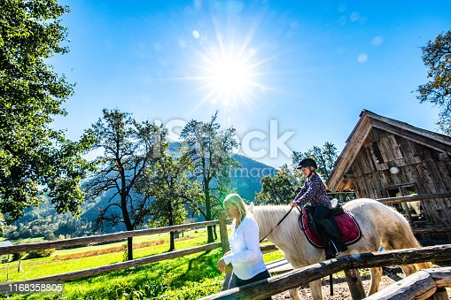 Girl training horseback riding with the help of her mother on ranch.