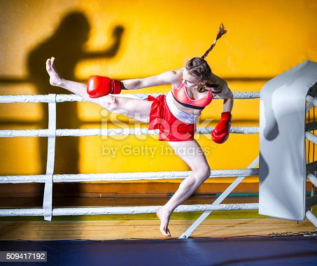 Athletic girl teenager dressed in sports uniform during a fight kickboxing. The girl in boxing stance sideways to the camera. She is jumping for boxing kick to the shadow of man. Shooting in the gym