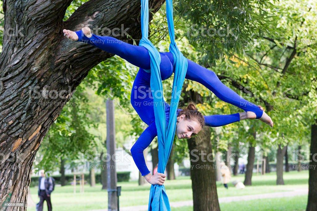 Girl training on silks on open air stock photo