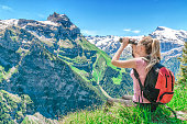 girl traveler examines through the binoculars the peak of Mount Engelberg, against the backdrop of the mountain peaks, admires the nature and the mountain scenery of Switzerland