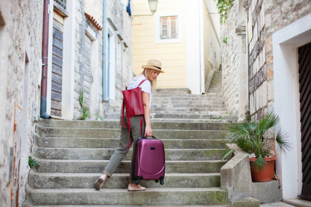 Girl traveler holds heavy suitcase on high stairs. Woman tourist carries luggage at old town street to authentic apartments. Concept of travel, summer vacation, solo female tourism, trip, adventure. stock photo