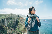 vintage photo of young asian girl traveler on road trip relaxing enjoy sea ocean view on mountain top. bixby creek bridge on highway 1 Big Sur area California USA. woman in sunglasses confident smile