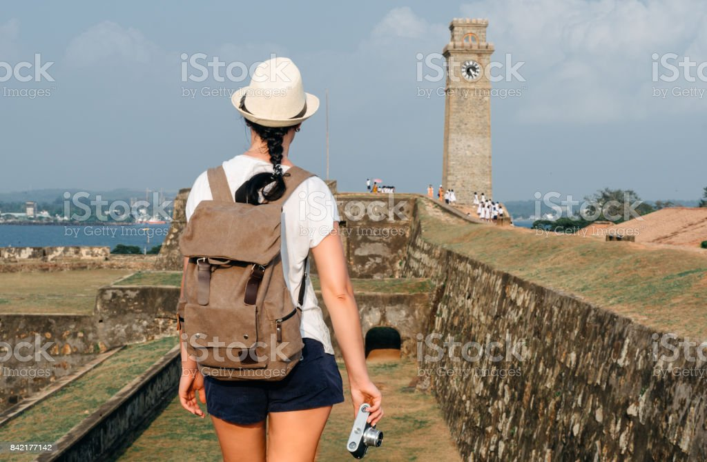 Girl traveler with a backpack and camera. City clock tower in the town of Galle in Sri Lanka. stock photo