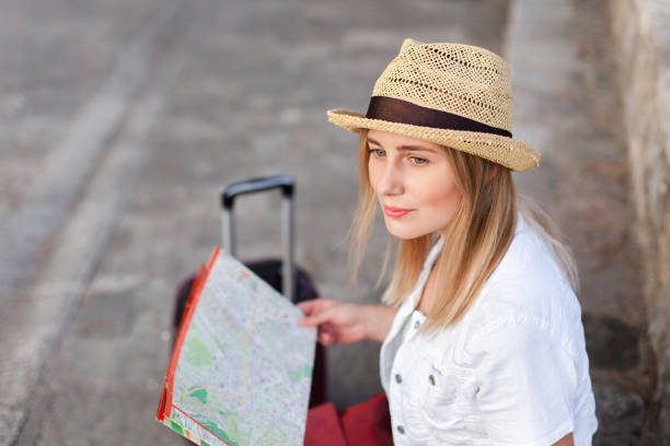 Girl traveler with city map at town street. Young woman tourist is waiting for transport on bus station, searching direction. Concept of travel, vacation, female tourism, adventure, trip, journey. stock photo