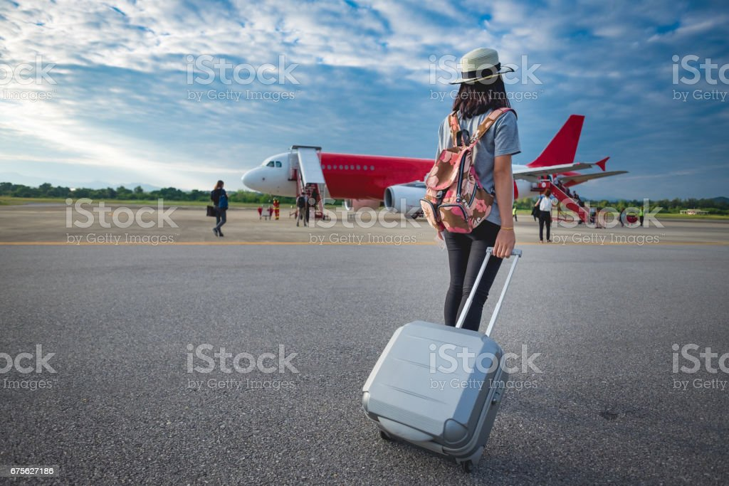 Girl traveler with luggage going to plane stock photo