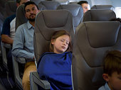 Portrait of a beautiful girl traveling by plane and sleeping during the flight - travel concepts