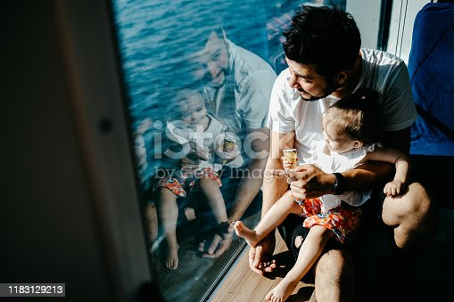 Girl traveling by ship with her father and looking through the window