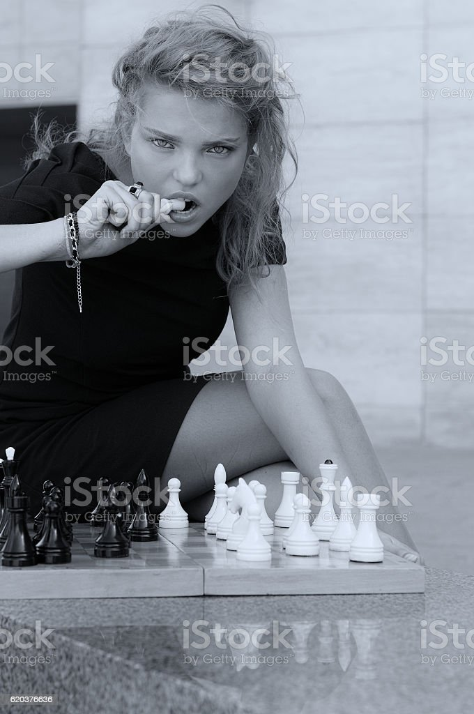 Girl tries to bite off the chess queen foto de stock royalty-free