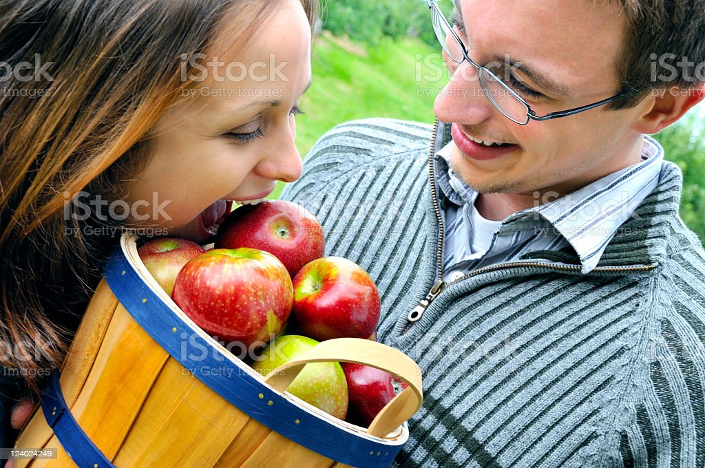 Girl Tries to Eat Apple Out of Basket stock photo