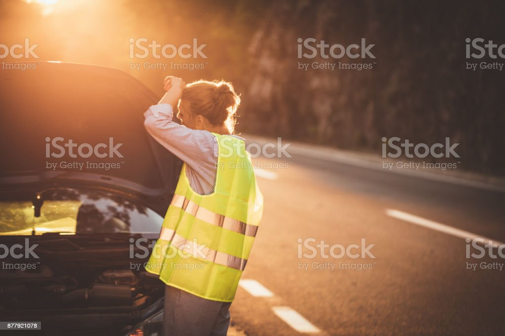 Girl tries to fix the car stock photo