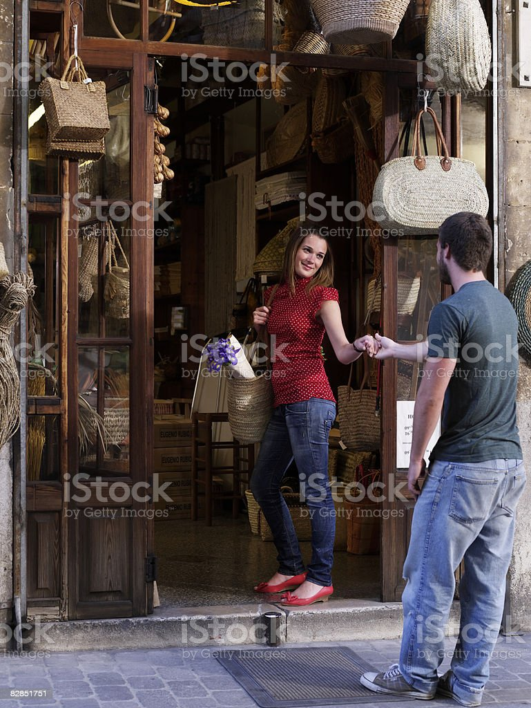Girl tries to pull boyfriend into shop royalty free stockfoto