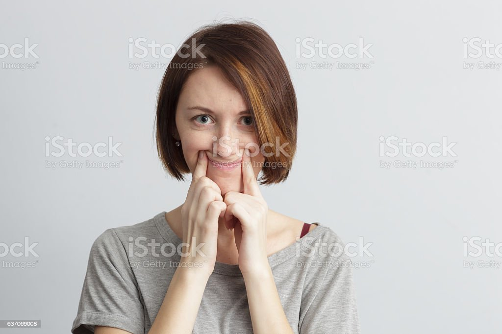 Girl tries to pull smile with fingers over her mouth. stock photo