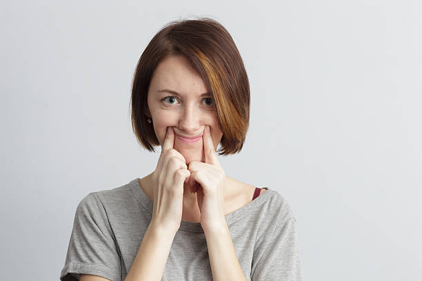 Girl tries to pull smile with fingers over her mouth. Girl tries to pull a smile with fingers over her mouth. Sad mood and pretense. cheesy grin stock pictures, royalty-free photos & images