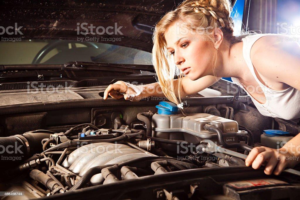 Girl tries to repair broken car stock photo
