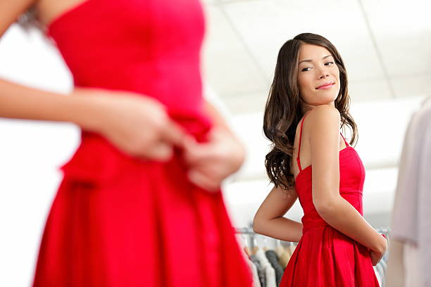 Girl trying dress Girl trying dress in looking in mirror cheerful and happy. Cute beautiful mixed race Asian / Caucasian young woman oin red dress. dress stock pictures, royalty-free photos & images