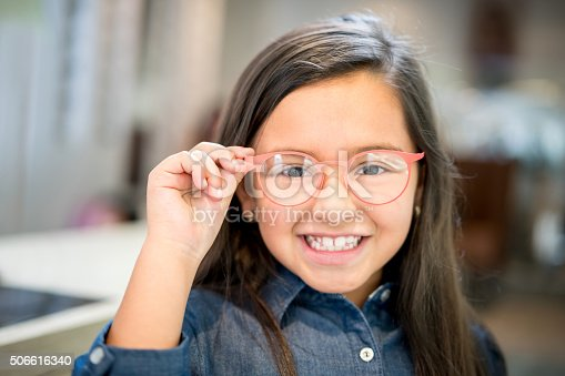 Little girl trying glasses at the optician - healthcare and medicine concepts
