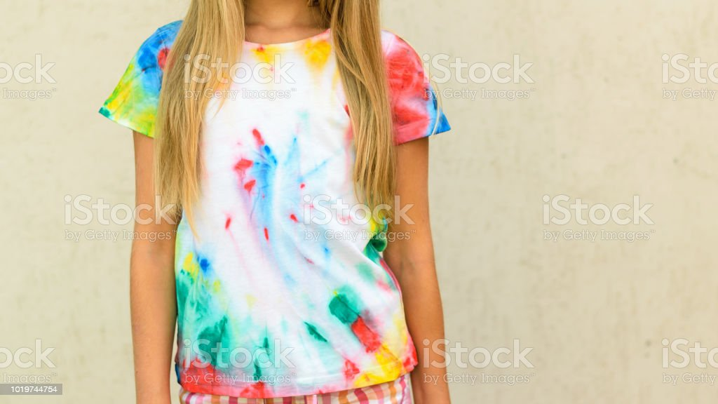 de703b6e Girl trying on a t-shirt painted in the style of tie dye. - Stock image .