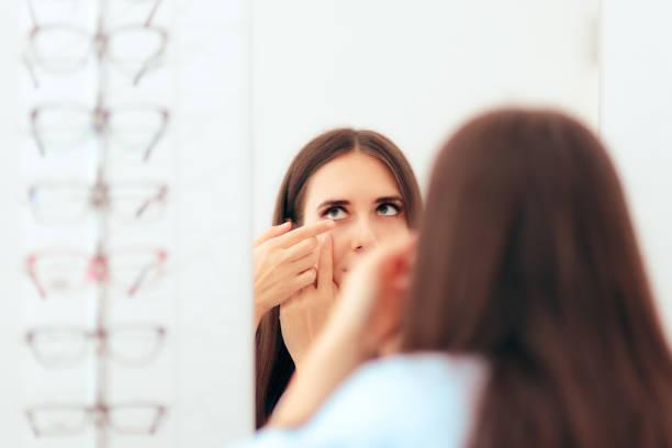 Jeune fille essayer des lentilles de Contact médical dans le miroir - Photo