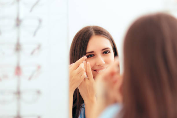 girl trying on medical contact lenses in the mirror - contacts imagens e fotografias de stock