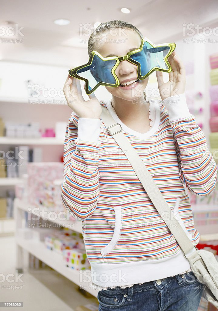 Girl trying on sunglasses in store royalty-free stock photo