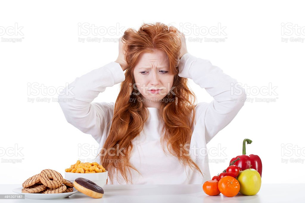 Girl trying to decide what to eat stock photo