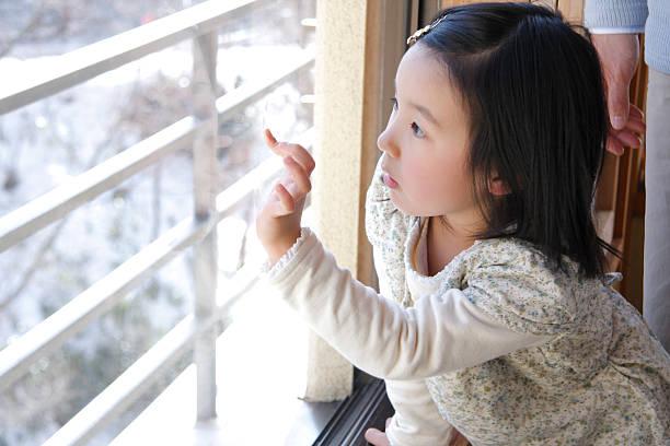 Girl intentando señalar imagen en una ventana - foto de stock