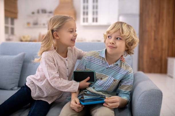 Girl trying to set boy ablaze, boy feeling surprised At home. Kids sitting on sofa, girl trying to hug boy, boy looks surprised ablaze stock pictures, royalty-free photos & images