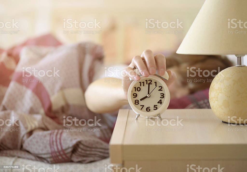 girl turns off the alarm clock stock photo