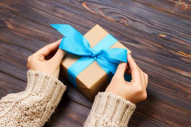 flicka knyta en enkel blå båge på en presentförpackning. insvept i vanligt kraftpapper och blått band. finputsning - blue yellow band bildbanksfoton och bilder