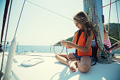Cute little girl sitting on the deck of sailing ships and she have fun while tied sailor's knot rabbit. The ship was sailing under the Ionian Sea in Greece and passes attractive Greek islands. The child was wearing a life jacket with sailor suit.