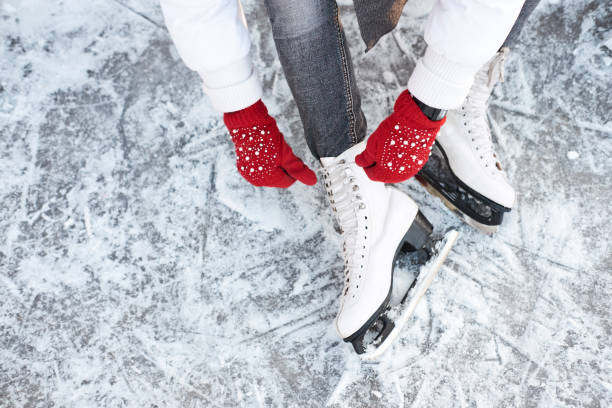 Girl tying shoelaces on ice skates before skating on the ice rink, hands in red knitted gloves. Girl tying shoelaces on ice skates before skating on the ice rink, hands in red knitted gloves. View from top. ice skating stock pictures, royalty-free photos & images