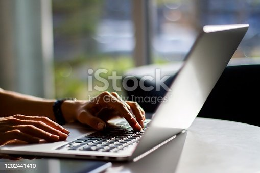 Girl typing on a laptop keyboard in a sunny interior, close up