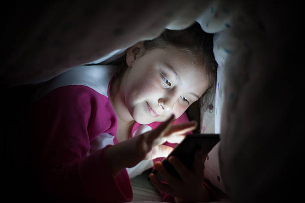 Girl under cover using tablet stock photo