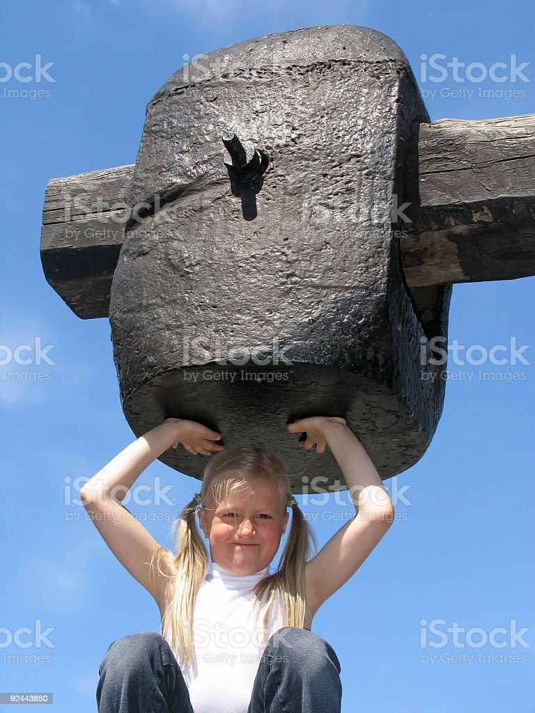 Girl under large hammer stock photo