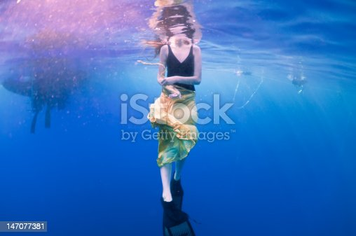 A fabulous girl in a beautiful dress in a pool swims and dreams on the background of bright lights. She holds a white cage in her hand and sinks to the bottom of the pool with her eyes closed. Portrait.