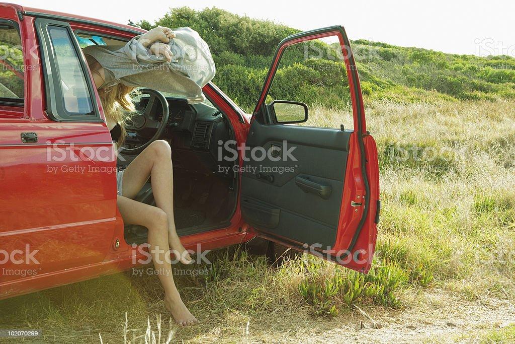 Girl undressing in car stock photo