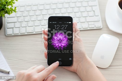 istock Girl unlock iPhone 6 Space Gray over the table 516205920
