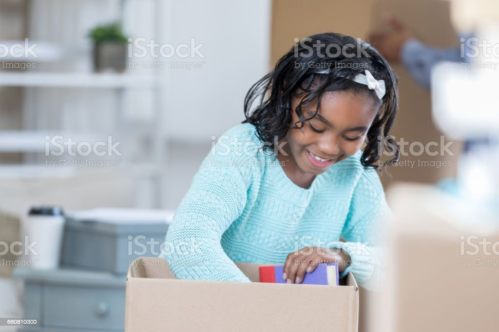 Girl unpacks box in new home stock photo