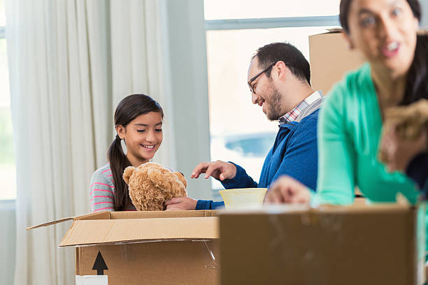 girl unpacks teddy bear from box in new home - happy mom packing some toys stock photos and pictures