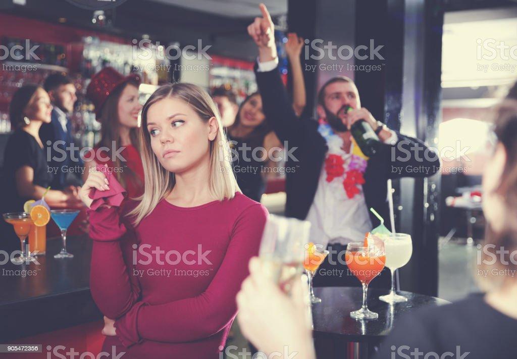 Menina chateada com o namorado bêbado na havaiana festa no bar - foto de acervo
