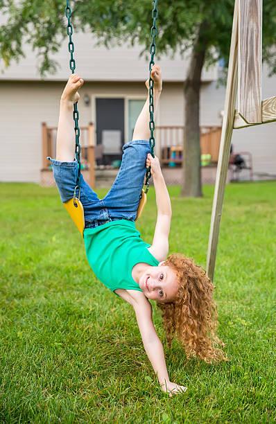 girl upside down on swing looking at camera - denim caprihosen stock-fotos und bilder