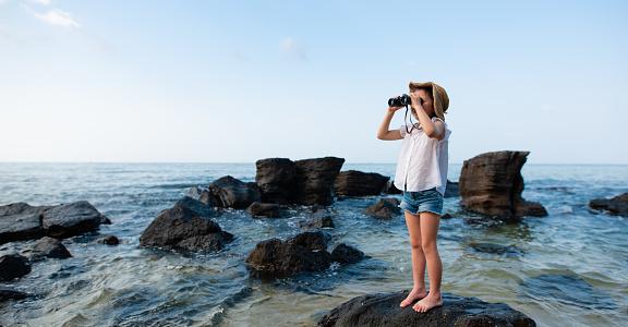 Girl use binoculars at the beach