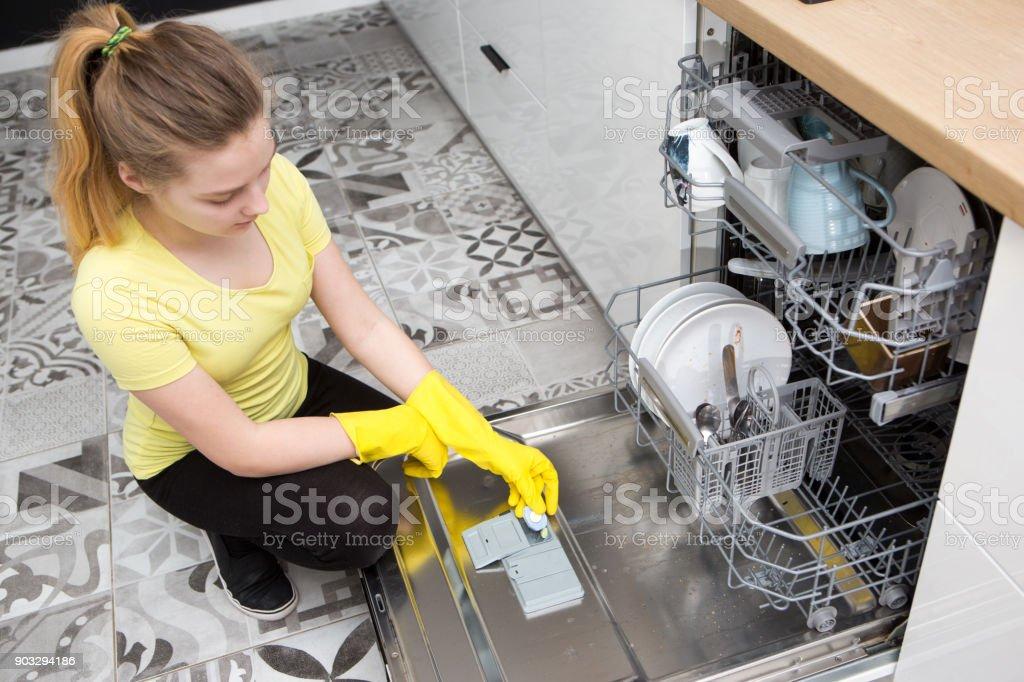 girl uses a dishwasher in the kitchen – zdjęcie