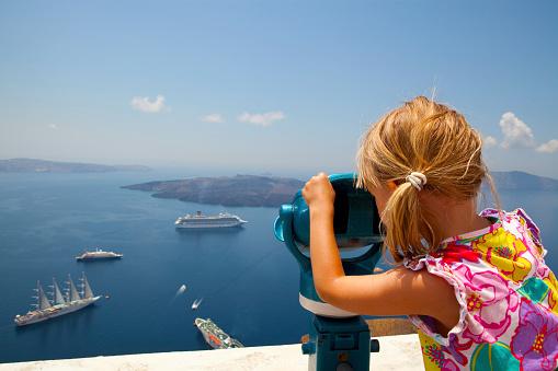 A girl uses binoculars above the sea in Santorini Greece