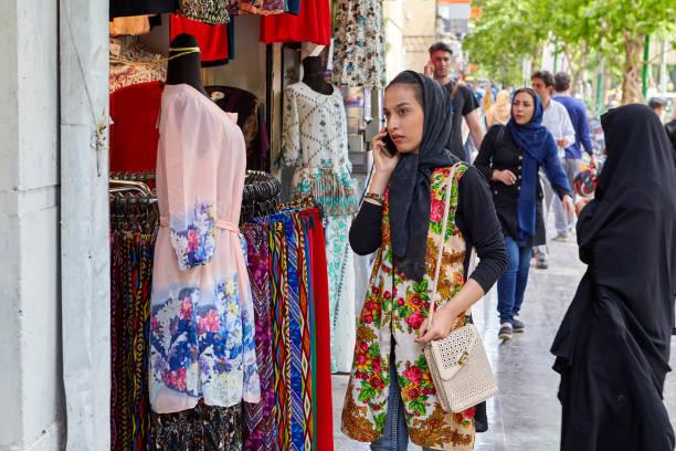 Jeune fille utilise smartphone près de magasin avec des vêtements lumineux, Ispahan, en Iran. - Photo