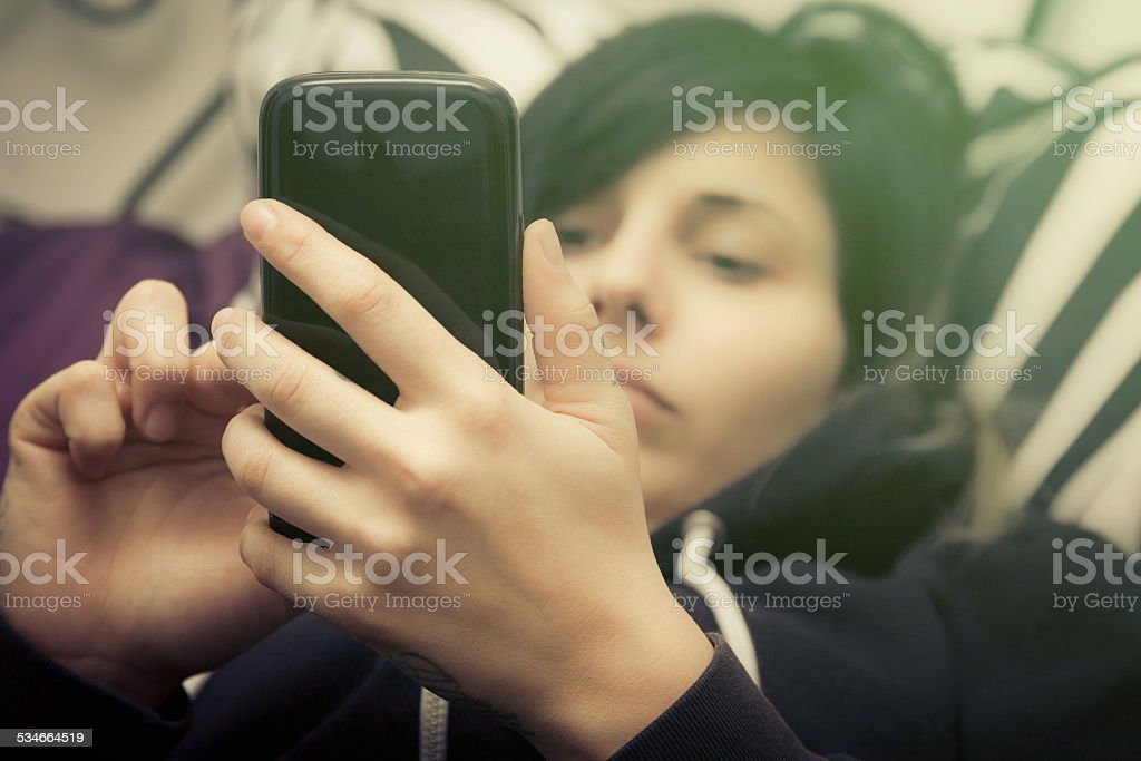 Girl uses smartphones to bed stock photo