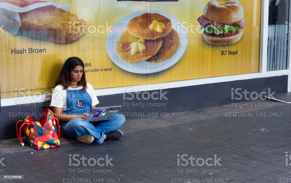 Girl using a laptop sitting on the street. stock photo