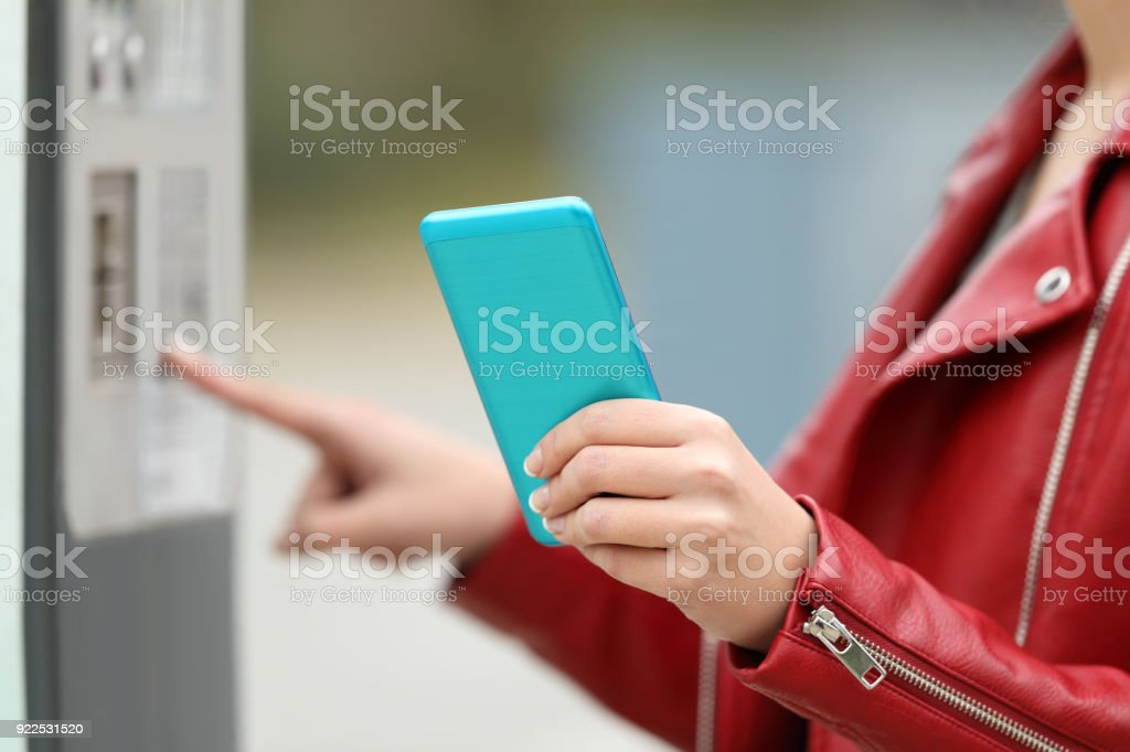 Girl using a smart phone to pay in a payment machine - foto stock