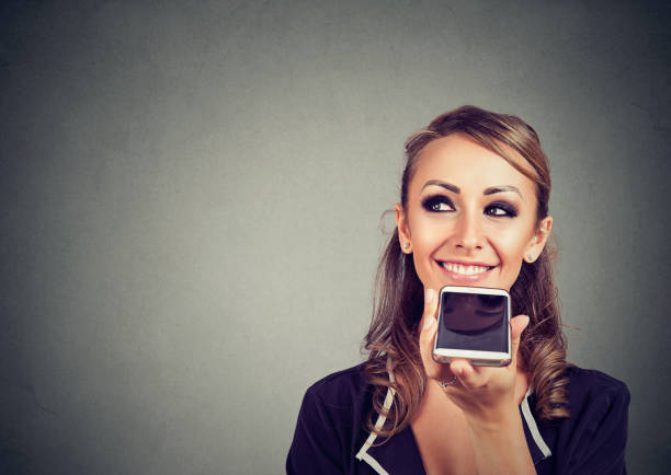 girl using a smart phone voice recognition function online on gray wall background - dictaphone stock pictures, royalty-free photos & images